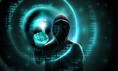 hacker in hoodie pointing to screen
