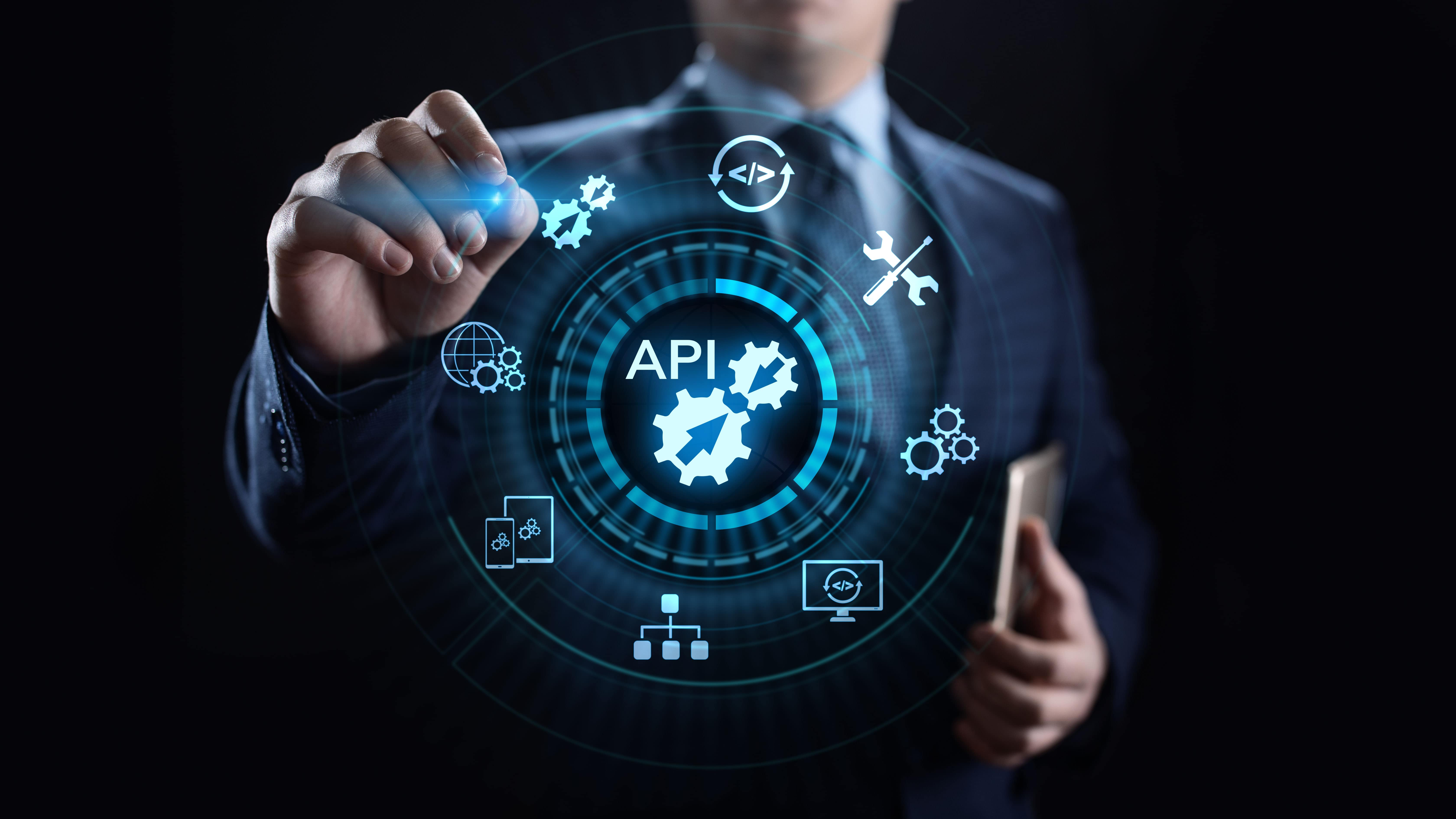 business man pointing to icons showing APIs and microservices
